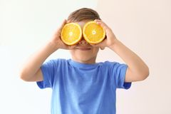 Cute little boy with halves of orange. On light background royalty free stock photo