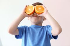 Cute little boy with halves of orange. On light background royalty free stock image