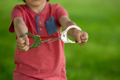 Cute little boy with the hand cuffs on his hands. Playing Stock Image