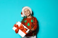Cute little boy in handmade Christmas sweater. And hat with gift on color background royalty free stock images