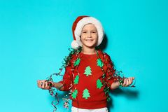 Cute little boy in handmade Christmas sweater. And hat with streamers on color background royalty free stock image