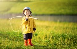 Cute little boy in hat holding big fishing net at the ready. Summer vacation concept stock images
