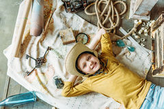 Cute little boy in hat lying on traveling map and smiling Stock Image