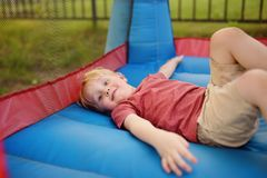 Cute little boy have fun in the leisure center for kids. Children`s sports in the open area. Baby lying on the trampoline. Cute little boy have fun in the royalty free stock image