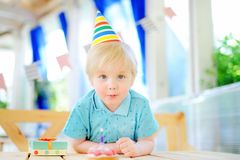 Cute little boy having fun and celebrate birthday party with colorful decoration and cake. Child with sweets, candy, whistle/blower/horn and festive gifts Royalty Free Stock Photo
