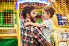 Cute little boy having fun with his dad. At the entertainment centre royalty free stock images