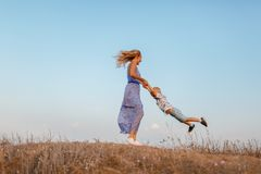 A cute little boy having fun with his mother on a bank of a river on a natural blurred background. royalty free stock photography