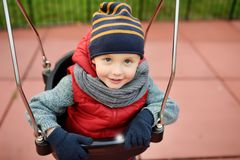 Cute little boy having fun on outdoor playground. Child on swing. Cute little boy having fun on outdoor playground. Spring/summer/autumn active sport leisure for stock photography