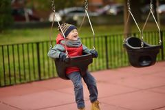 Cute little boy having fun on outdoor playground. Child on swing. Cute little boy having fun on outdoor playground. Spring/summer/autumn active sport leisure for royalty free stock images