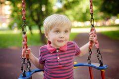 Cute little boy having fun on outdoor playground. Child on swing. Cute little boy having fun on outdoor playground. Summer active sport leisure for kids. Child stock photos
