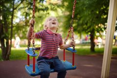 Cute little boy having fun on outdoor playground. Child on swing. Cute little boy having fun on outdoor playground. Summer active sport leisure for kids. Child stock photo