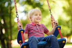 Cute little boy having fun on outdoor playground. Child on swing. Cute little boy having fun on outdoor playground. Summer active sport leisure for kids. Child royalty free stock image