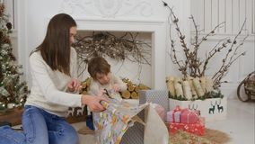 Cute Little Boy Helping His Mother To Cut Paper For Wrapping Up Christmas Presents Royalty Free Stock Image