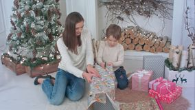 Cute little boy helping his mother to cut paper for wrapping up Christmas presents. Professional shot on BMCC RAW with high dynamic range. You can use it e.g Stock Image