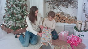 Cute little boy helping his mother to cut paper for wrapping up Christmas presents stock footage