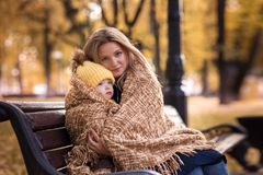 Cute little boy with her mother autumn. Cute little boy with her mother walking in the autumn in the park in the yellow foliage and sitting in a rug Stock Photo