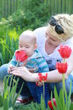 Cute little boy with her mother smelling fresh tulip Royalty Free Stock Image