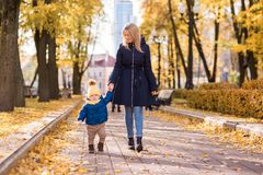 Cute little boy with her mother autumn. Cute little boy with her mother walking in the autumn in the park in the yellow foliage and sitting in a rug Stock Photos