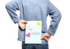 Cute little boy hiding greeting card for Mother`s Day. Behind his back, on white background Stock Images