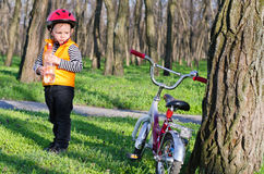 Cute little boy with his bike in woodland Stock Photos