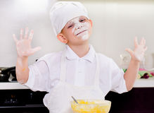 Cute little boy with his face covered in flour Stock Photo