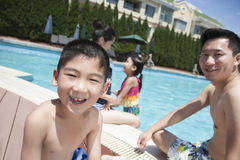 Cute little boy and his family playing in the pool Stock Photos
