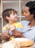 Cute little boy and his father cutting bread Stock Photo