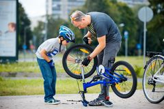 Cute little boy with his father repairing bicycle outdoors stock images