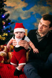 Cute little boy and his father sitting at Christmas tree Stock Photography