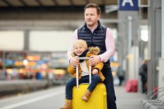Cute little boy and his father waiting express train on railway station platform Stock Photos