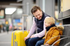 Little boy and his father waiting express train on railway station platform or waiting their flight at the airport Royalty Free Stock Photos
