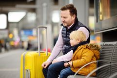 Little boy and his father waiting express train on railway station platform or waiting their flight at the airport. Cute little boy and his father waiting Stock Photos