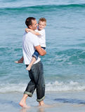 Cute little boy and his father walking on the sand Stock Images