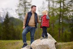 Cute little boy and his father walks in Swiss national Park on spring. Hiking with little kids. Cute little boy and his father walks in Swiss national Park on royalty free stock images