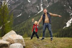 Cute little boy and his father walks in Swiss national Park on spring. Hiking with little kids. Dangerous situation: standing on stock image
