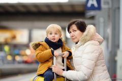 Cute little boy and his grandmother/mother waiting express train on railway station platform Royalty Free Stock Images