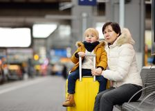 Cute little boy and his grandmother/mother waiting express train on railway station platform. Travel, tourism, winter vacation and family concept. Mature women stock image