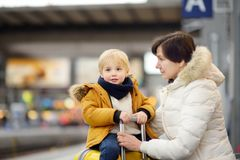 Cute little boy and his grandmother/mother waiting express train on railway station platform royalty free stock photos