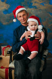 Cute little boy and his grandpa sitting at Christmas tree Stock Image