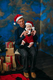 Cute little boy and his grandpa sitting at Christmas tree Stock Photography