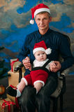 Cute little boy and his grandpa sitting at Christmas tree Royalty Free Stock Photo