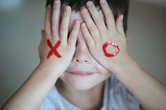 The cute little boy with his hands covering the eyes with the XO symbol royalty free stock image