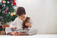 Cute little boy and his monkey toy, playing on tablet Royalty Free Stock Image