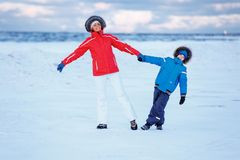 Cute little boy and his mother on icy beach Royalty Free Stock Images