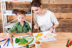 Cute little boy and his mother paiting bright pictures together stock image