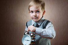 Cute little boy holding alarm clock Royalty Free Stock Image