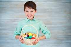 Cute little boy holding basket with colorful eggs after easter egg hunt Royalty Free Stock Photography