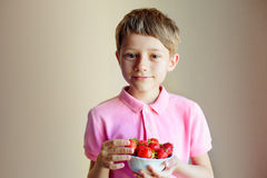 Cute little boy holding bowl with strawberries royalty free stock photos