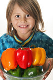 Cute little boy holding colorful peppers Stock Photo