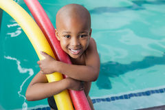 Cute little boy holding foam rollers by the pool Royalty Free Stock Image